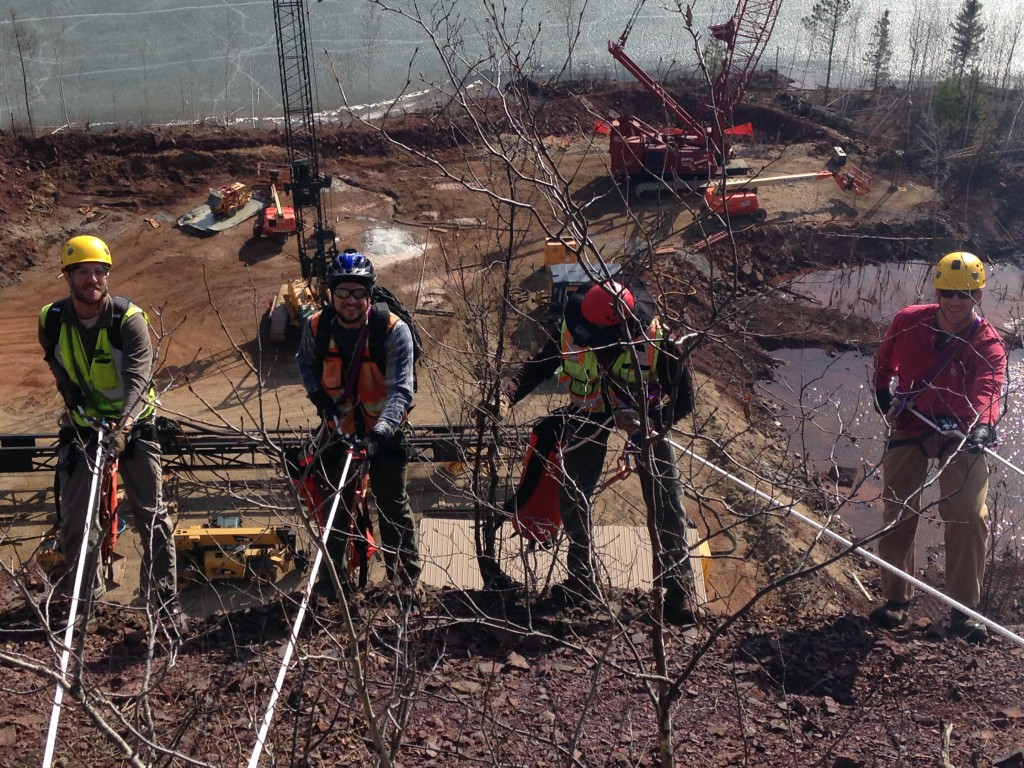 DBA engineers prepare to go over the edge of the 200-ft tall west wall of the Rouchleau mine pit with the load test site in the background. From left to right: David Graham, Nathan Glinski, Ryan Turner, and Paul Axtell